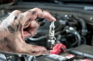 An auto mechanic holds an old, dirty spark plug over a car engin