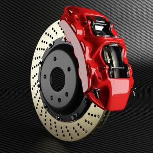 Automobile Brake Disk And Red Caliper On Carbon Background